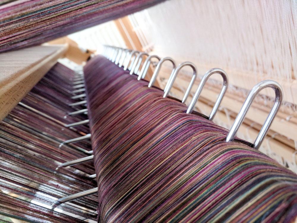 Looking inside a fully warped sectional beam with a dark plum purple and colour mix warp on it, looking toward the light. Sectional rakes are visible.