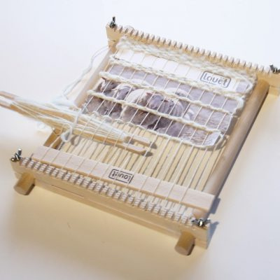 Image of a small frame loom from the top. Loom is warped with stick shuttle loaded and work on the loom.