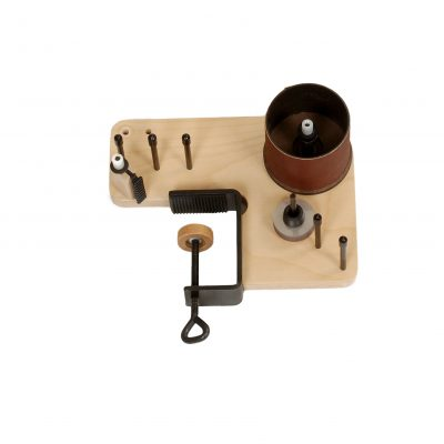 Image of a tension regulator device with sandpaper cylinder and wood clamp.