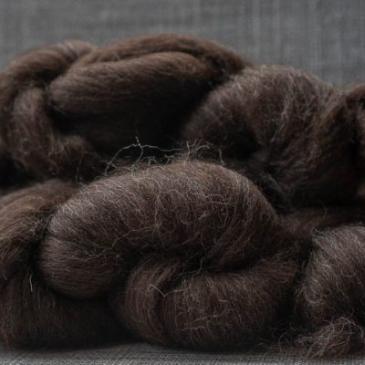 Dark brown spinning fibre on white linen background.