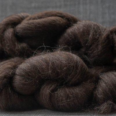 Dark brown spinning fibre on white linen background.