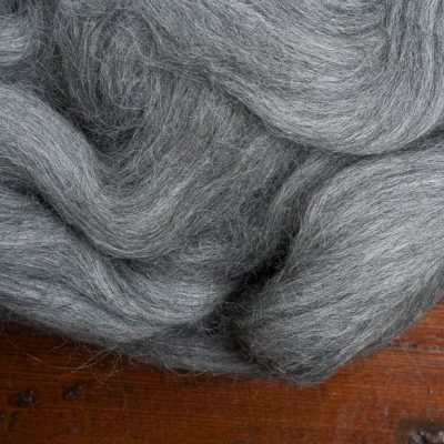 Grey spinning fibre on a rich wood background.