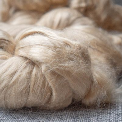 Light golden, very soft spinning fibre on a grey linen background.