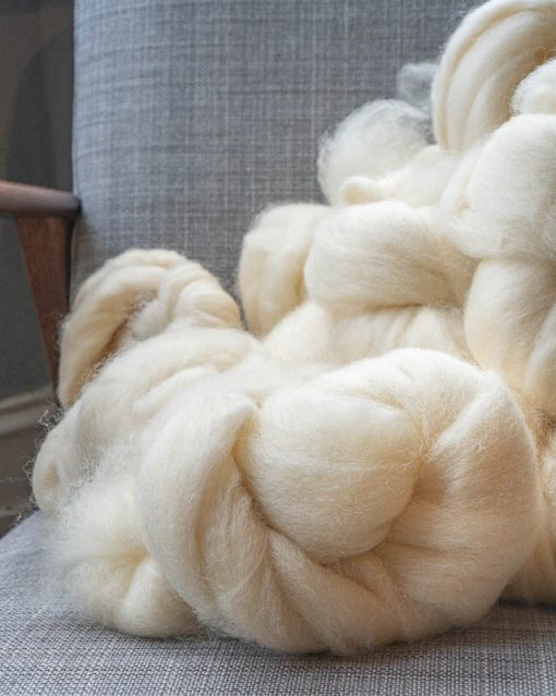 Cream spinning fibre on a grey linen background.