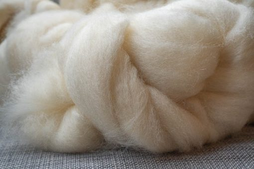 Cream spinning fibre on a grey linen background.